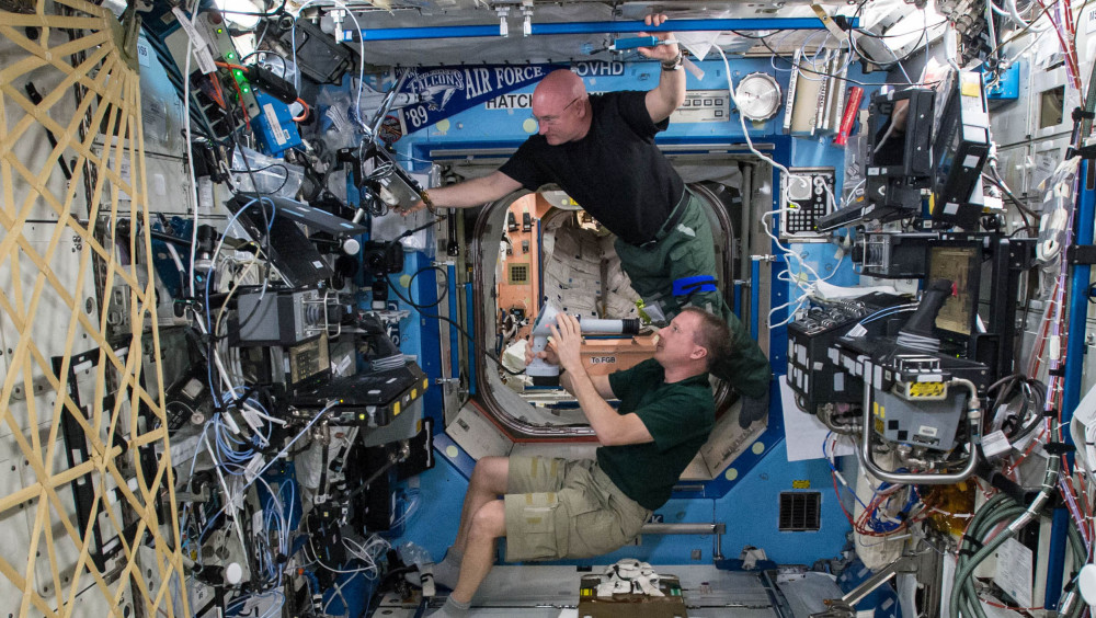 Astronauts Terry Virts, bottom, and Scott Kelly perform eye exams to study vision health last April in the Destiny Laboratory of the International Space Station. Kelly sees his nearly completed one-year mission as a steppingstone to Mars.