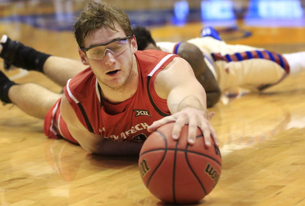 Texas Tech forward Matthew Temple reaches for a loose ball during the first half of the Red Raiders' 67-58 loss to No. 2 Kansas on Saturday in Lawrence, Kansas.