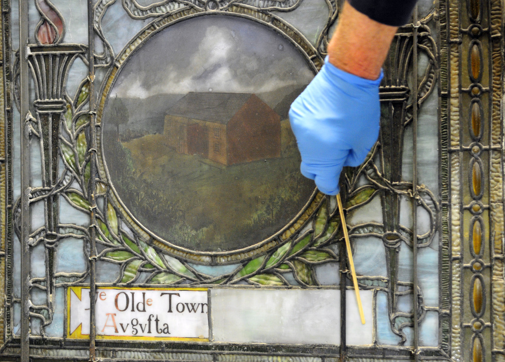One of the unrestored windows from Lithgow Public Library on Thursday at Stained Glass Express in Manchester. Robert Bolton said that the solid white piece beside the square reading Old Town Augusta probably used to have more words on it.