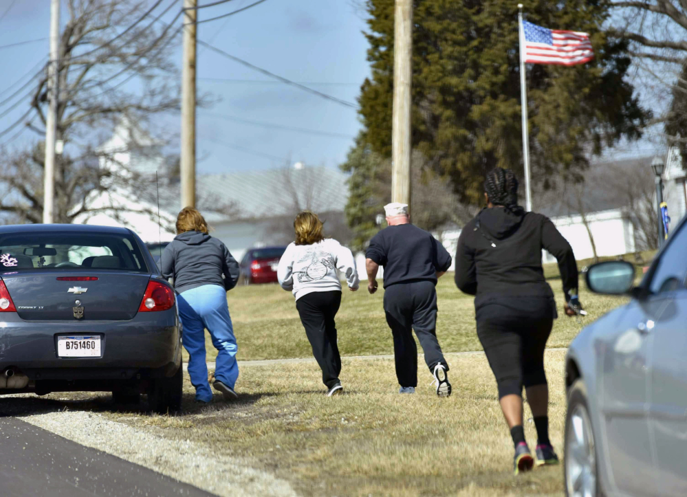 Parents run to see if they are allowed to pick up their children Monday after a school shooting at Madison Local Schools in Madison Township in Butler County, Ohio.