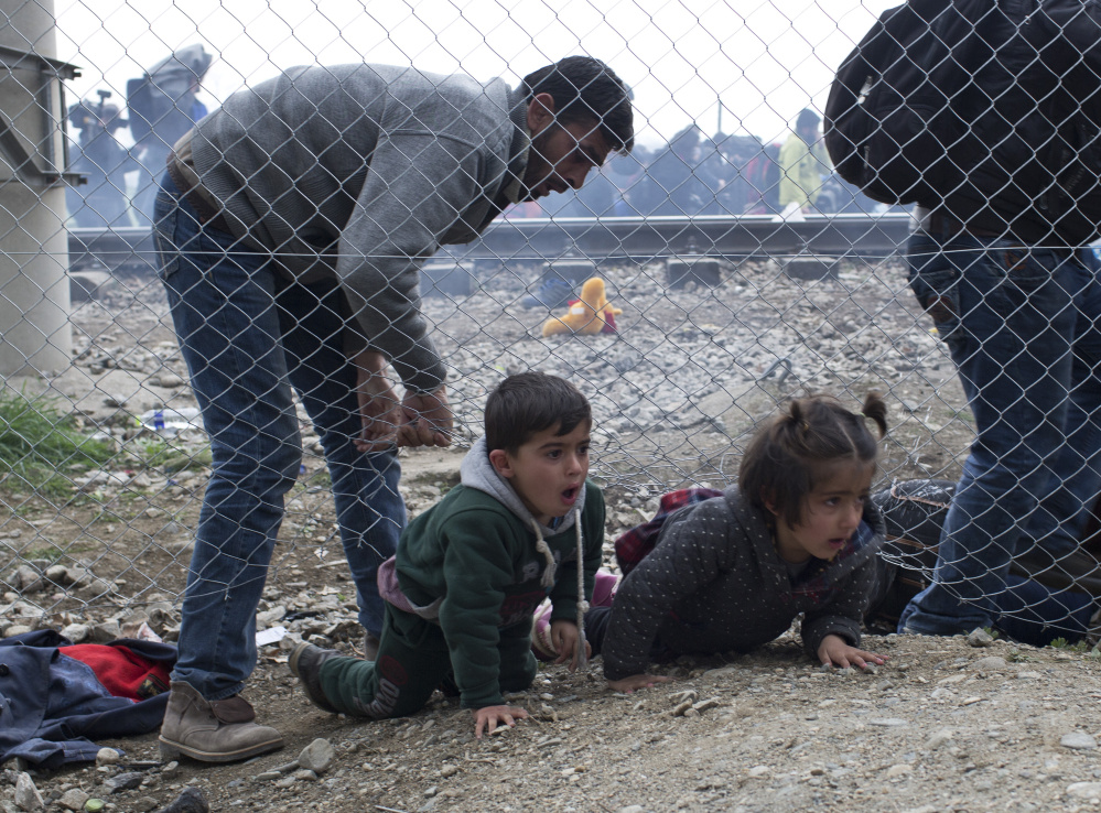 A man helps children to run away after Macedonian police fired tear gas at a group of the refugees and migrants who tried to push their way into Macedonia, breaking down a border gate near the northern Greek village of Idomeni on Monday.