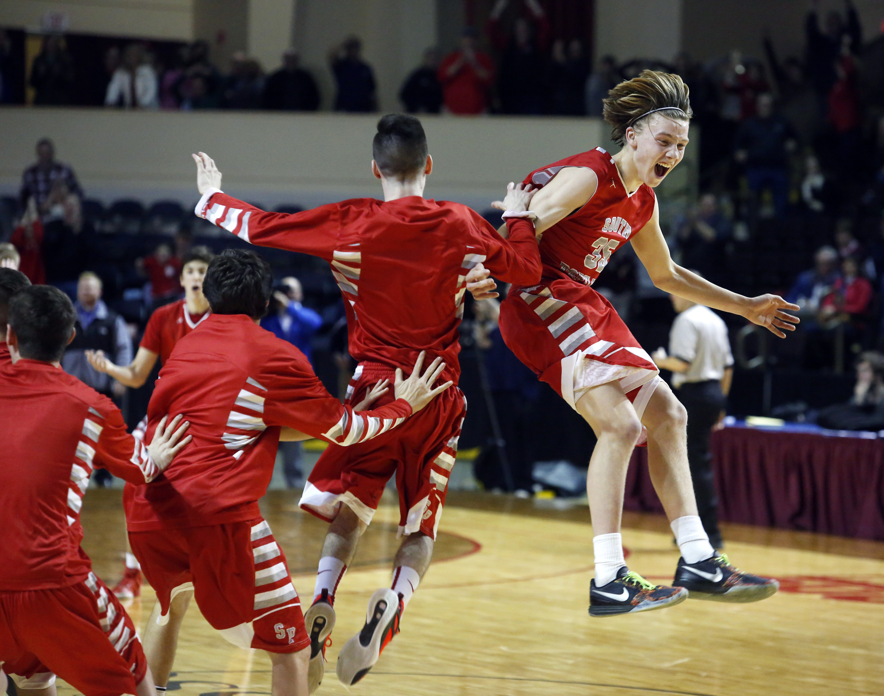 Riley Hasson of South Portland celebrates with teammates after defeating Massabesic in the Class AA South final Friday night at the Cross Insurance Arena. Derek Davis/Staff Photographer