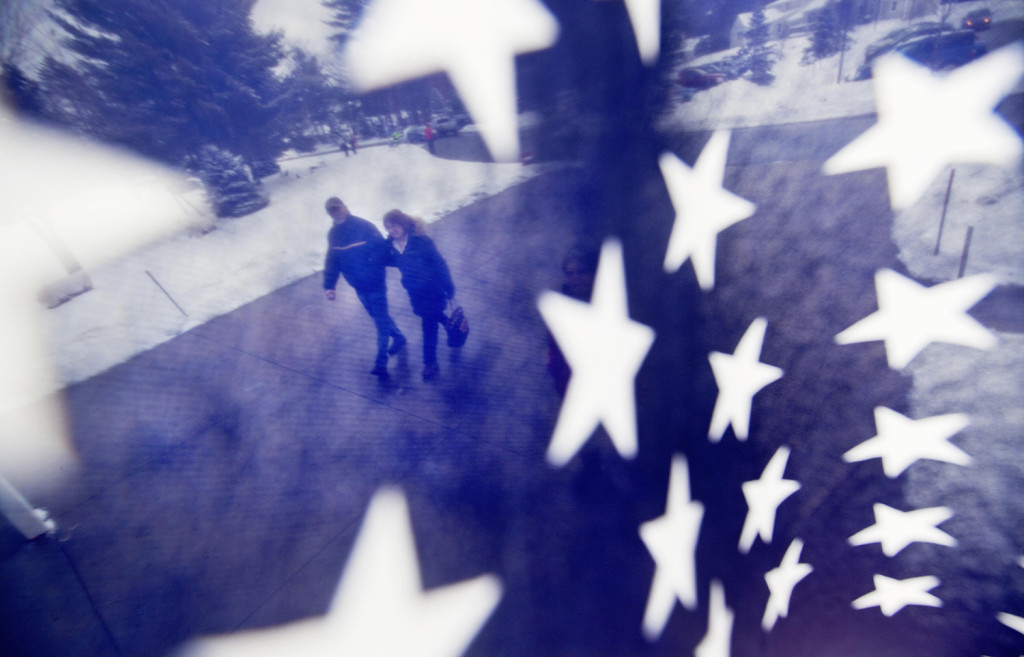 A couple is seen through an American flag as they walk to a polling place for the New Hampshire primary, Tuesday in Nashua, N.H. The Associated Press
