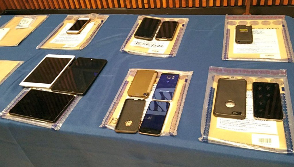 A collection of Apple iPhones and iPads fill a table during a news conference at New York City Police Headquarters, Thursday. Police and prosecutors say that the top-notch encryption technology on Apple mobile phones is now routinely hindering criminal investigations. The Associated Press
