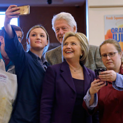 Democratic presidential candidate Hillary Clinton and her husband, former President Bill Clinton, pose for a selfie with employees at Market Basket supermarket on Tuesday in Manchester, N.H.