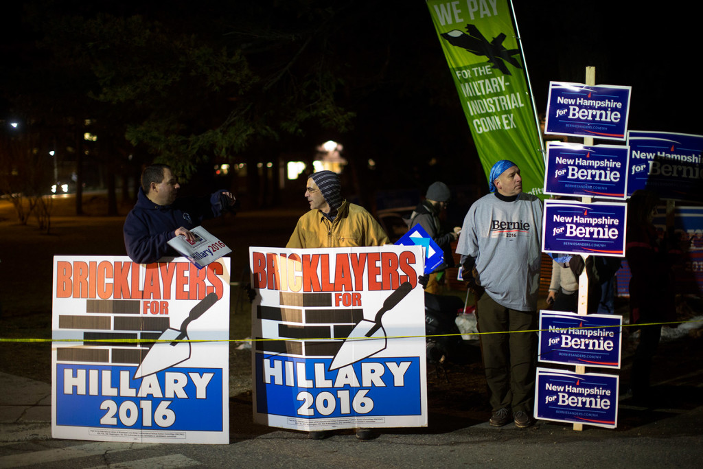Backers of Hillary Clinton and Bernie Sanders show competing signs before the debate.