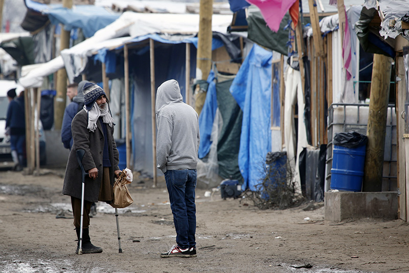 Migrants speak in a makeshift camp near Calais, France on Friday.