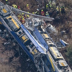 Rescue workers comb through wreckage at the site of a train collision near Bad Aibling, Germany, Tuesday. Photo by Peter Kneffel/dpa via AP