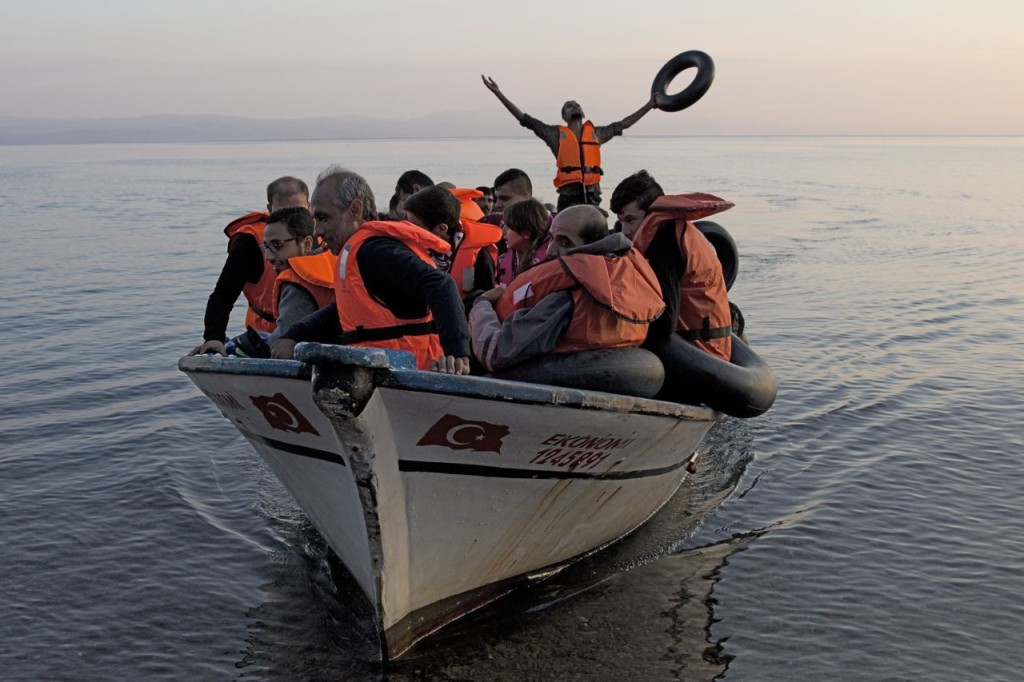 A Syrian refugee thanks god as he arrives with others from Turkey on the shores of the Greek island of Lesbos. The International Organization for Migration says nearly 2,000 people per day have reached Europe by sea since Jan. 1. The Associated Press