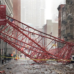 Debris and a mangled crane lie in the street in New York's Tribeca neighborhood in Lower Manhattan following a deadly collapse on Friday, Feb. 5, 2016. (AP Photo/Colleen Long)