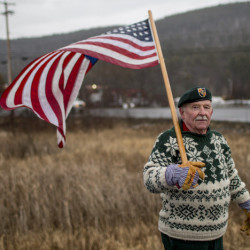 DERRY, NH - FEBRUARY 3: John Jones, 75, (cq) of Sutton Mills, N.H., a former green beret, holds an American flag while standing on Route 120 on the outskirts of Hanover, N.H., Wednesday, February 3, 2016. Jones was standing the rain in support of Democratic presidential candidate Bernie Sanders. (Photo by Gabe Souza/Staff Photographer)