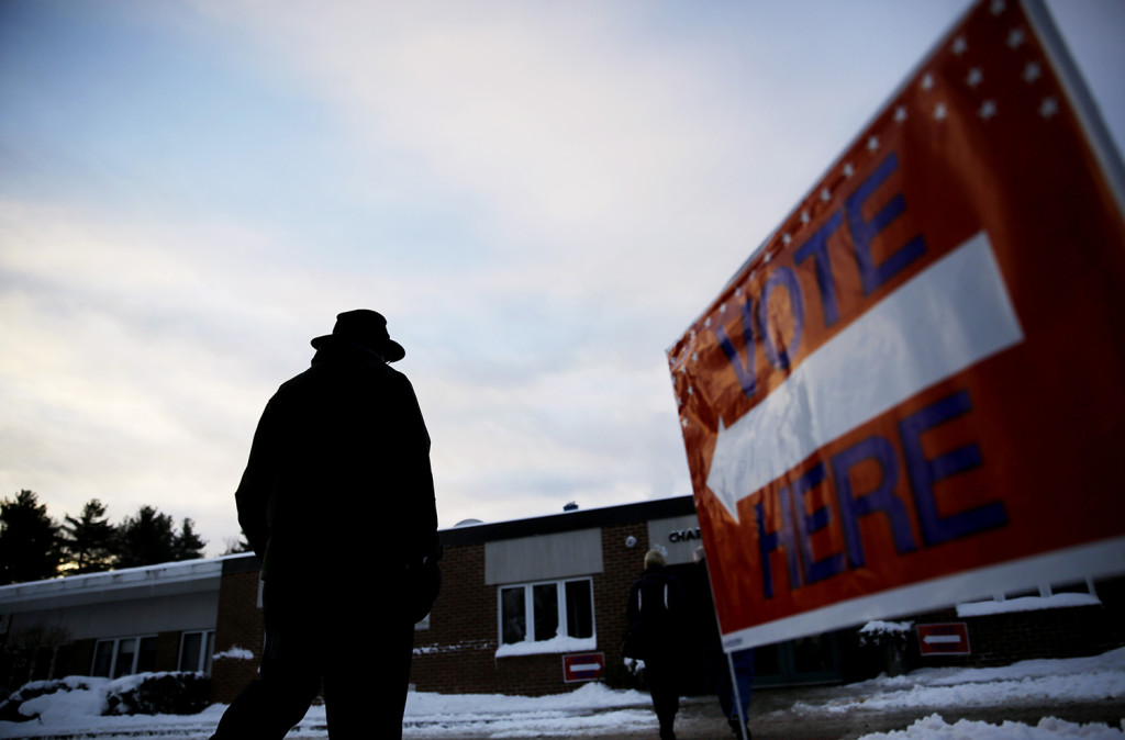 A voter walks in to a polling site at dawn to cast a ballot in the New Hampshire primary Tuesday in Nashua, N.H. The Associated Press