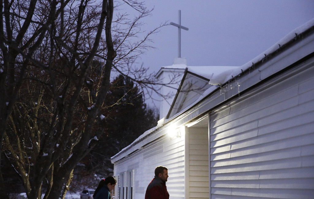 A voter walks in to a polling site at a church at dawn to cast a ballot in the New Hampshire primary, Tuesday in Nashua, N.H. The Associated Press