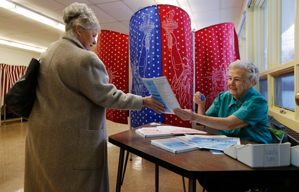 A voting official hands a voter a blank Democratic ballot as the woman arrives to cast her vote in Manchester.