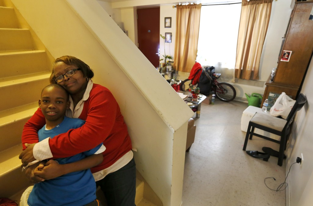 Debra Aldridge, right, poses for a portrait with her grandson, Mario Hendricks, at her home on Chicago's South Side.  The Associated Press