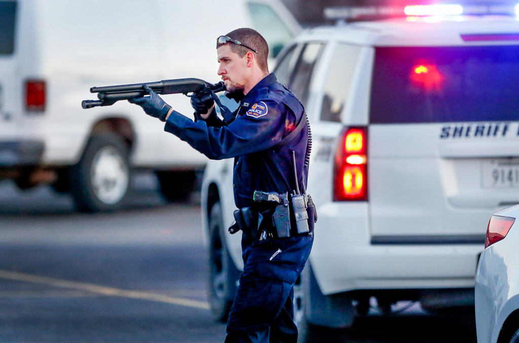 Police go through the parking lot of Excel Industries on Thursday in Hesston, Kan., where a gunman killed four people and injured many more. Fernando Salazar/The Wichita Eagle via AP