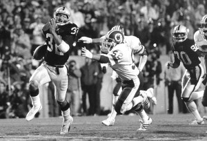 FILE - In this Jan. 22, 1984, file photo, Los Angeles Raiders running back Marcus Allen (32) outruns Washington Redskins  Neal Olkewicz (52) for a touchdown during Super Bowl XVIII at Tampa Stadium in Tampa,  Fla. Allen scored two touchdowns during the game and was named Most Valuable Player as his team won 38-9. (AP Photo/File)