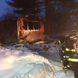 Firefighters work at the scene of Monday's fire on a private road off Snow Hill Road in New Gloucester.