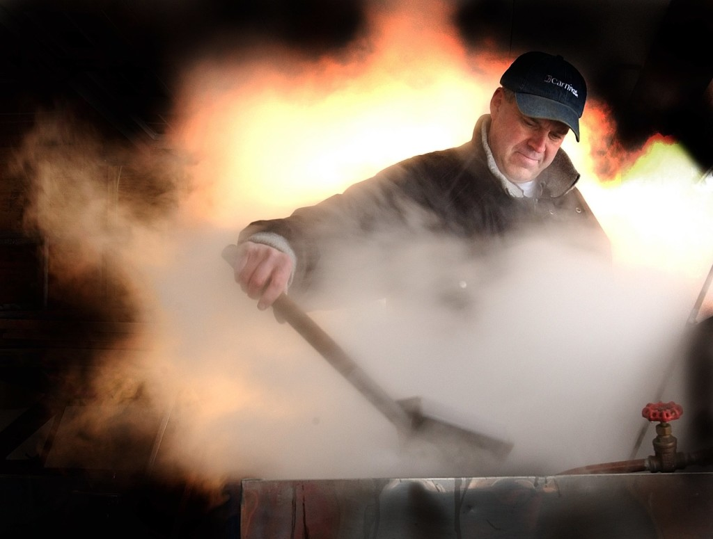 George Phelps of Gardiner skims the tanks of his home made sap boiler as he creates maple syrup in his garage. Some maple syrup producers have asked the FDA to crack down on businesses claiming their products contain maple syrup when they do not.  Photo by Fred J. Field