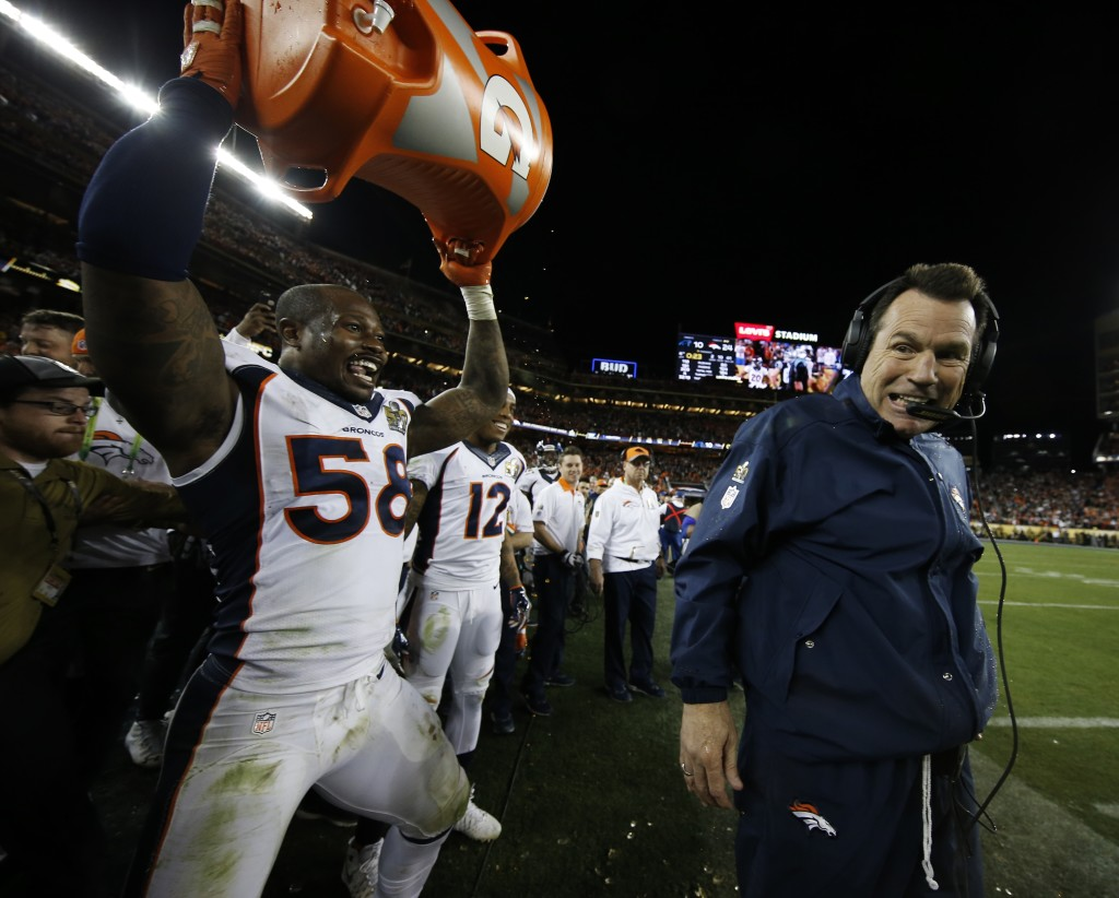 Denver head coach Gary Kubiak, right, reacts after getting soaked with a sports drink by Von Miller (58) after their win against the Carolina Panthers in Super Bowl 50 on Sunday in Santa Clara, Calif. The Broncos won 24-10. The Associated Press