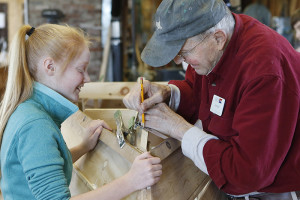 Boatbuilders - one experienced, one learning - John Hall and Nuala Glendinning work on a Yankee Tender at the Maine Maritime Museum boat shop.