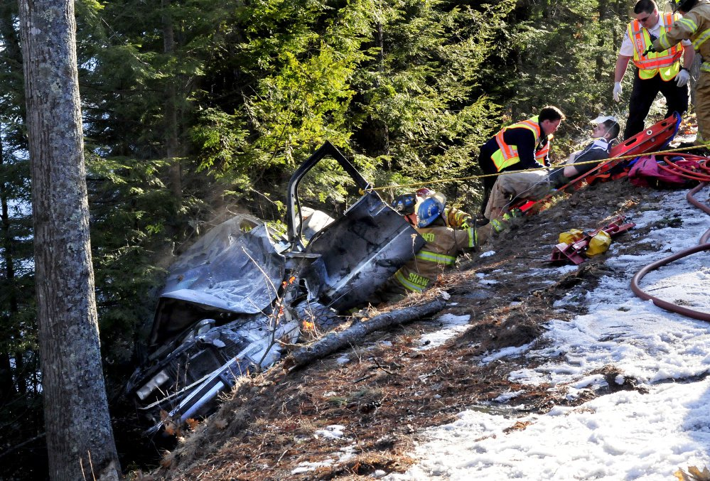 Firefighters pull an injured man strapped in a gurney up a steep embankment after he was removed from his vehicle.