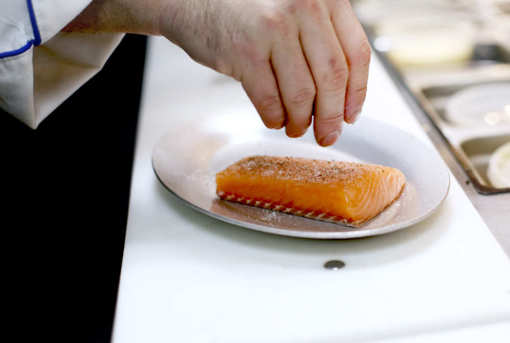 Bo Byrne, exectuive chef at Tiqua, seasons a fillet of salmon for Salmon Au Puy, a French dish.