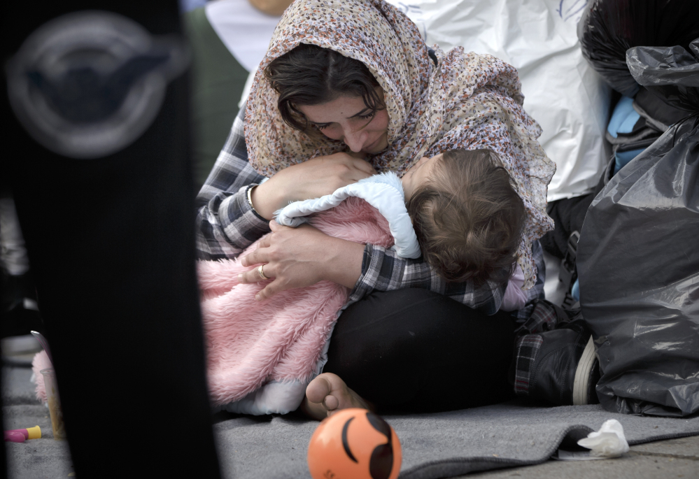 A migrant woman cries while holding a baby in Athens on Monday. Border restrictions farther north in the Balkans have left thousands of refugees stranded in Greece.
