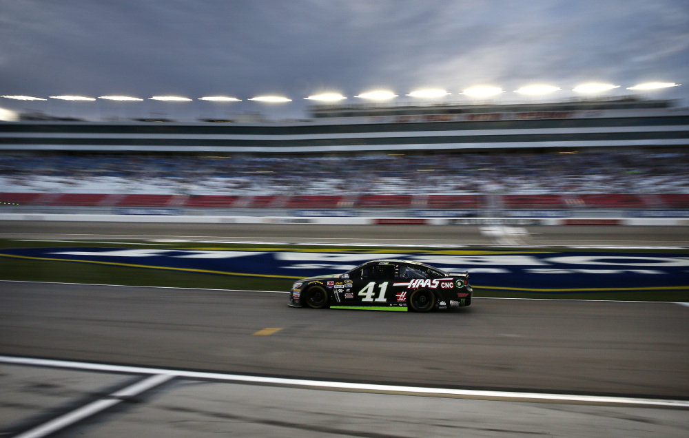 In this photo taken with a slow shutter speed, Kurt Busch drives out of pit row during qualifying for a NASCAR Sprint Cup Series auto race Friday in Las Vegas.