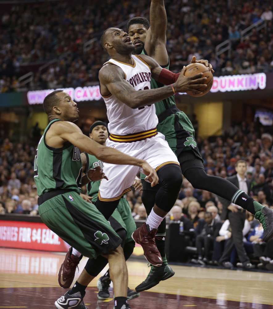 Cleveland's LeBron James, center, drives to the basket against Boston's Avery Bradley, left, and Amir Johnson during the Cavaliers' 120-103 win Saturday in Cleveland.
