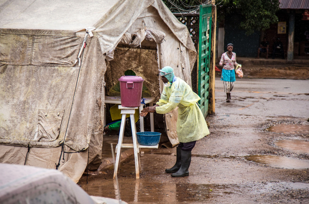 In this Aug. 11, 2014, file photo, a health worker cleans his hands with chlorinated water before entering an Ebola screening tent at the government hospital in Kenema, Sierra Leone.