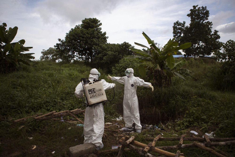 In this Sept. 24, 2014, file photo, a health worker sprays a colleague with disinfectant after working inside a morgue with people suspected of dying from the Ebola virus, in Kenema, eastern Sierra Leone.