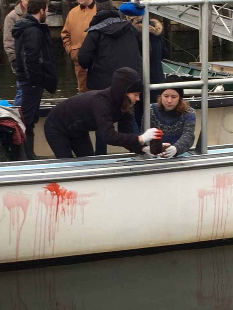 "Crew members of the horror film ""Island Zero"" apply fake blood to a lobster boat in Camden Harbor last week."