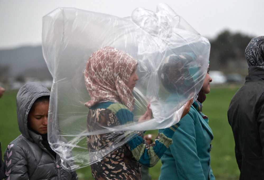 A migrant girl shields herself from the rain while waiting for food rations at the northern Greek border station of Idomeni on Monday. The EU wants Turkey to help ease the crisis that has left thousands encamped in the wintry cold on the Greece-Macedonia border.