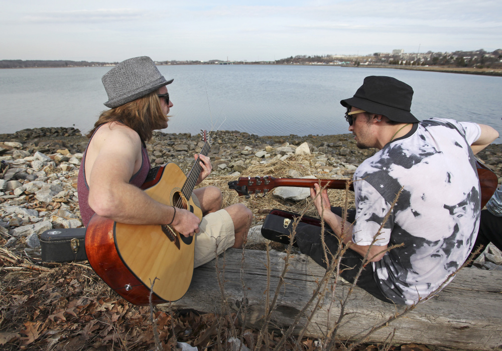 P.J. Moon of North Carolina and Ollie Hewat of Colorado, who are both currently living in Portland, enjoy the view along Back Cove and the mild temperatures Wednesday while they practice songs for their new band.