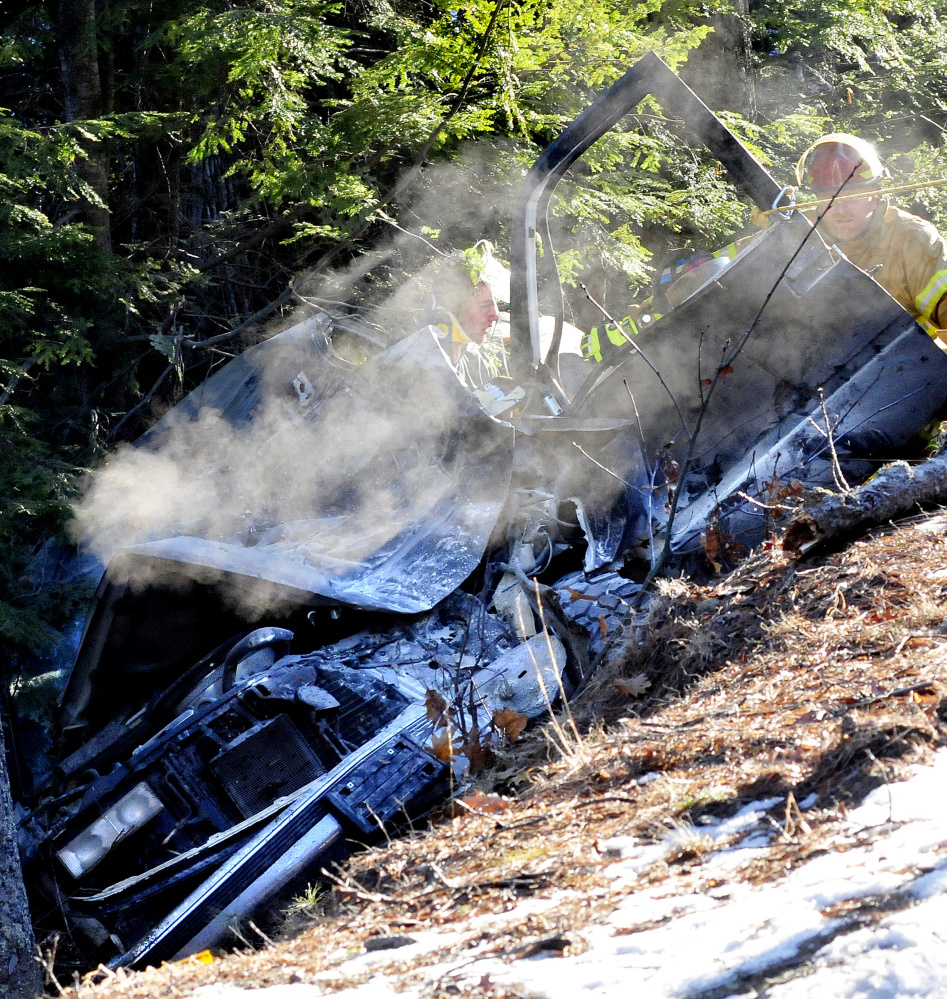 Smoke continues to rise from Eric Bachand's vehicle as firefighters stabilize him after his vehicle went off Route 135 in Belgrade on Tuesday. A Maine State Police trooper used a fire extinguisher to put out the fire before firefighters arrived.