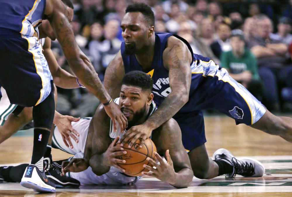 The Associated Press Amir Johnson of the Celtics, bottom, grabs a loose ball as Memphis forward P.J. Hairston, right, tries to knock it free during the second quarter Wednesday night in Boston.