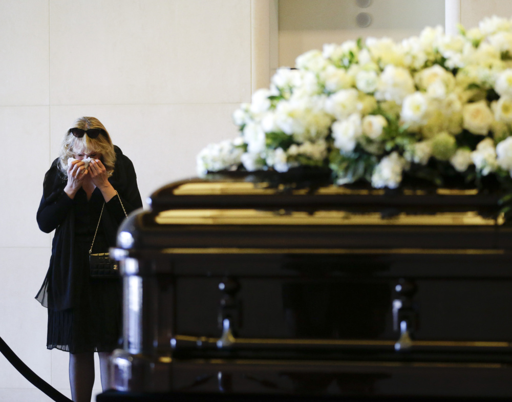 A woman wipes a tear away as she pauses beside the casket of Nancy Reagan at the Ronald Reagan Presidential Library in Simi Valley, California, on Wednesday.