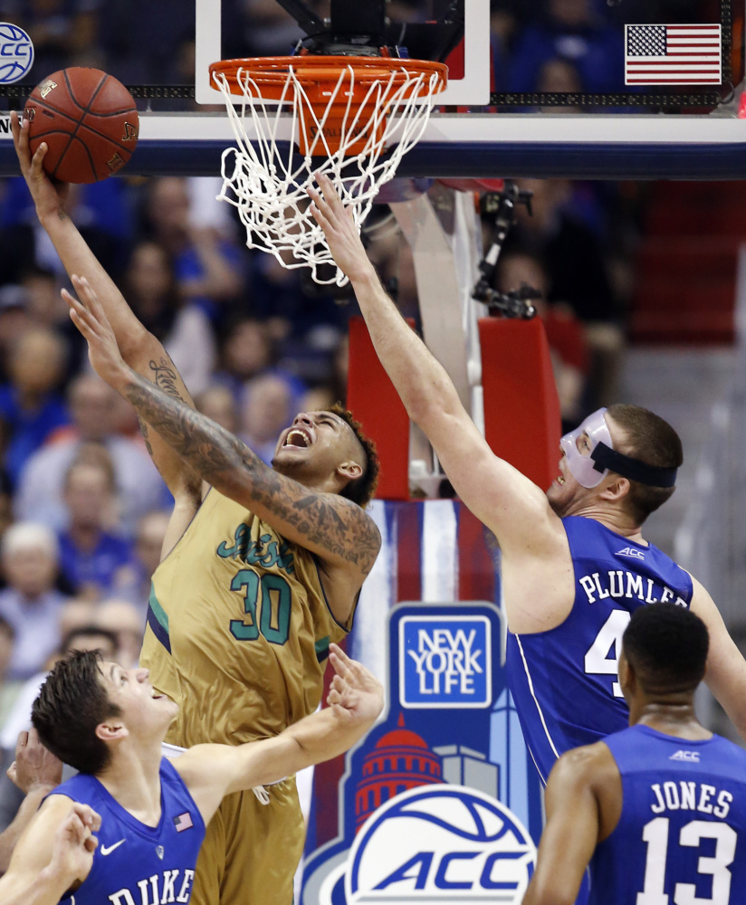 Notre Dame forward Zach Auguste rises from a sea of Blue Devils to score during the second half of Thursday's 84-79 victory over Duke in the ACC tournament.