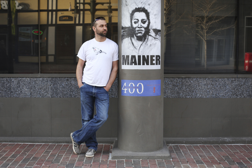 """Street artist Orson Horchler, who goes by the name Pigeon, stands by posters he designed for the exhibition """"400 Years of New Mainers"""" at the Maine Historical Society in Portland."""