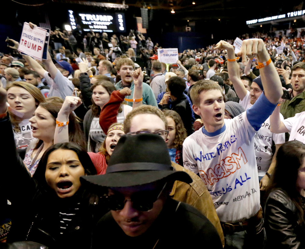 Protesters of Republican presidential candidate Donald Trump, right, chant after a rally on the campus of the University of Illinois-Chicago, was canceled due to security concerns Friday, March 11, 2016, in Chicago.