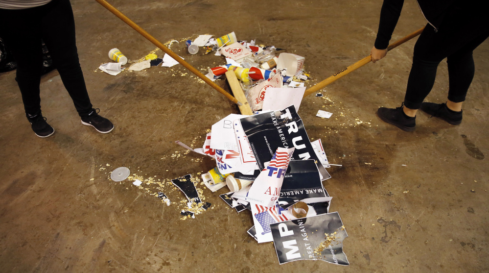 The Associated Press Trash is scooped up, including torn campaign signs for Republican presidential candidate Donald Trump, after a rally for Trump was canceled due to security concerns, on the campus of the University of Illinois-Chicago, Friday, March 11, 2016, in Chicago.