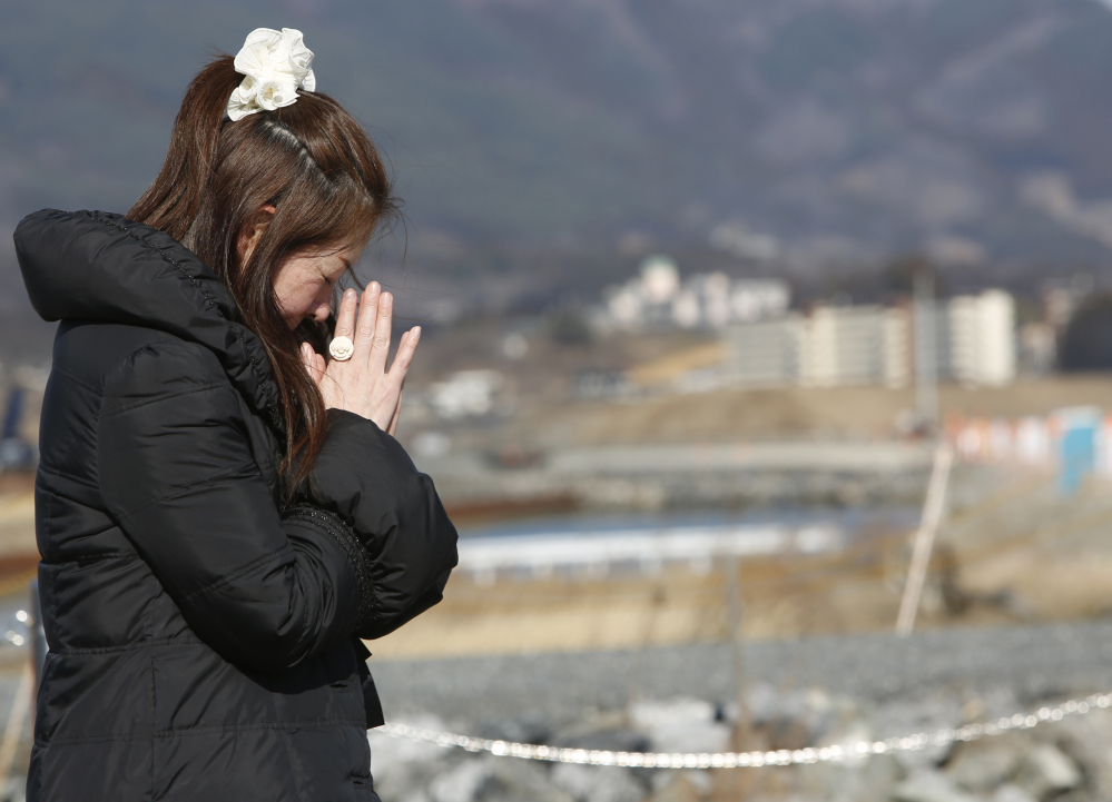 A woman prays Friday in Rikuzentakata, Iwate Prefecture, in northeastern Japan. It was the anniversary of the deadly tsunami that slammed the coast there five years ago.