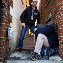 Kirk Carlsen, an outreach worker for the Milestone Foundation HOME Team, awaits help from his partner while trying to revive a passed-out homeless man in an alley off Middle Street, east of Franklin Street.