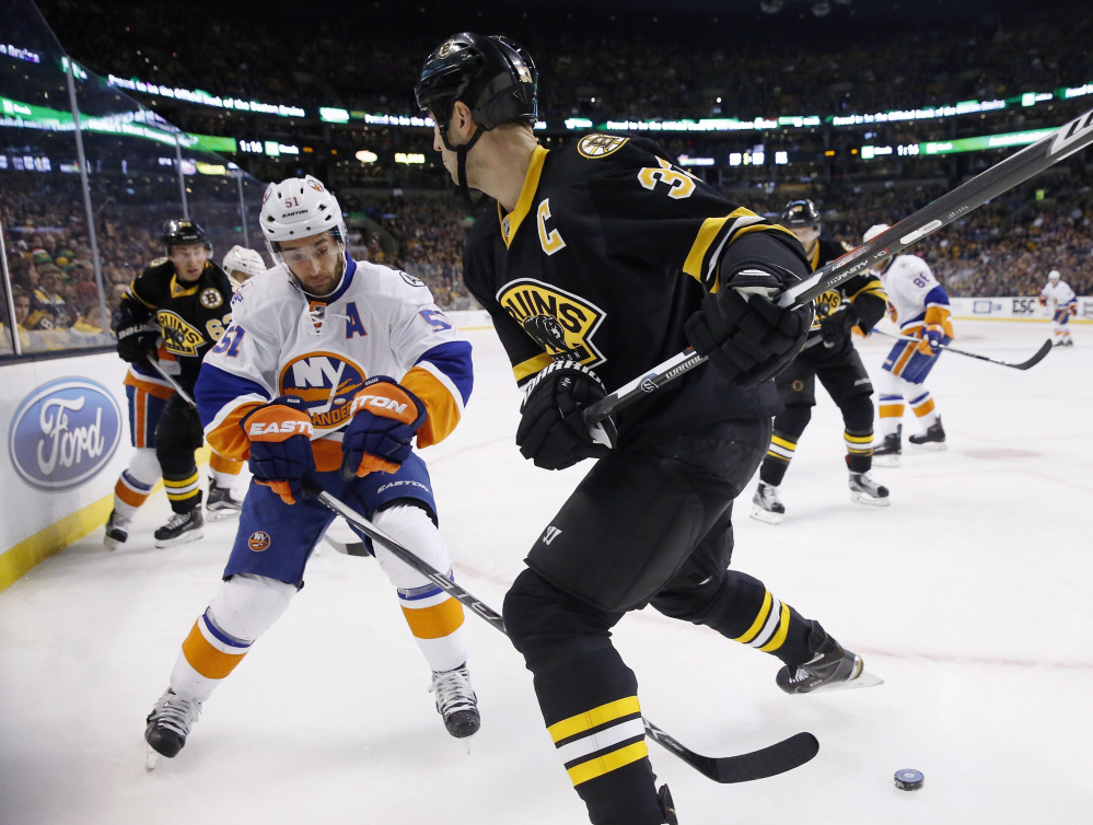 Boston's Zdeno Chara, right, prepares to check New York's Frans Nielsen during the Bruins' 3-1 win Saturday in Boston.