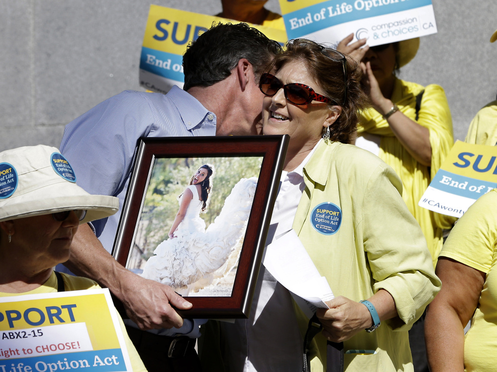 Elizabeth Wallner, who is dying of colon cancer, is hugged by Dan Diaz after she spoke at a rally calling for California Gov. Jerry Brown to sign the right-to-die legislation Sept. 24 at the Capitol in Sacramento. Diaz is holding a photo of his late wife, Brittany Maynard, the 29-year-old California woman with brain cancer who moved to Oregon to legally end her life. The measure's implementation was delayed in California and will go into effect in June of this year.