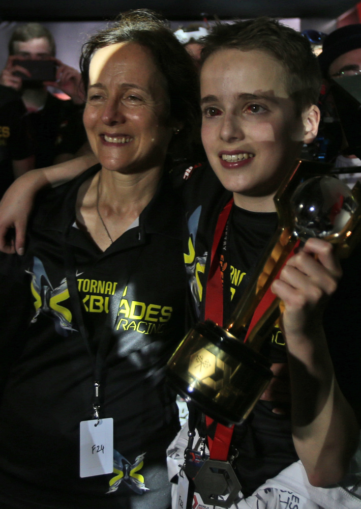 Luke Bannister, 15, of Somerset, England, with his mother, holds the first-prize trophy that he led his team to win.