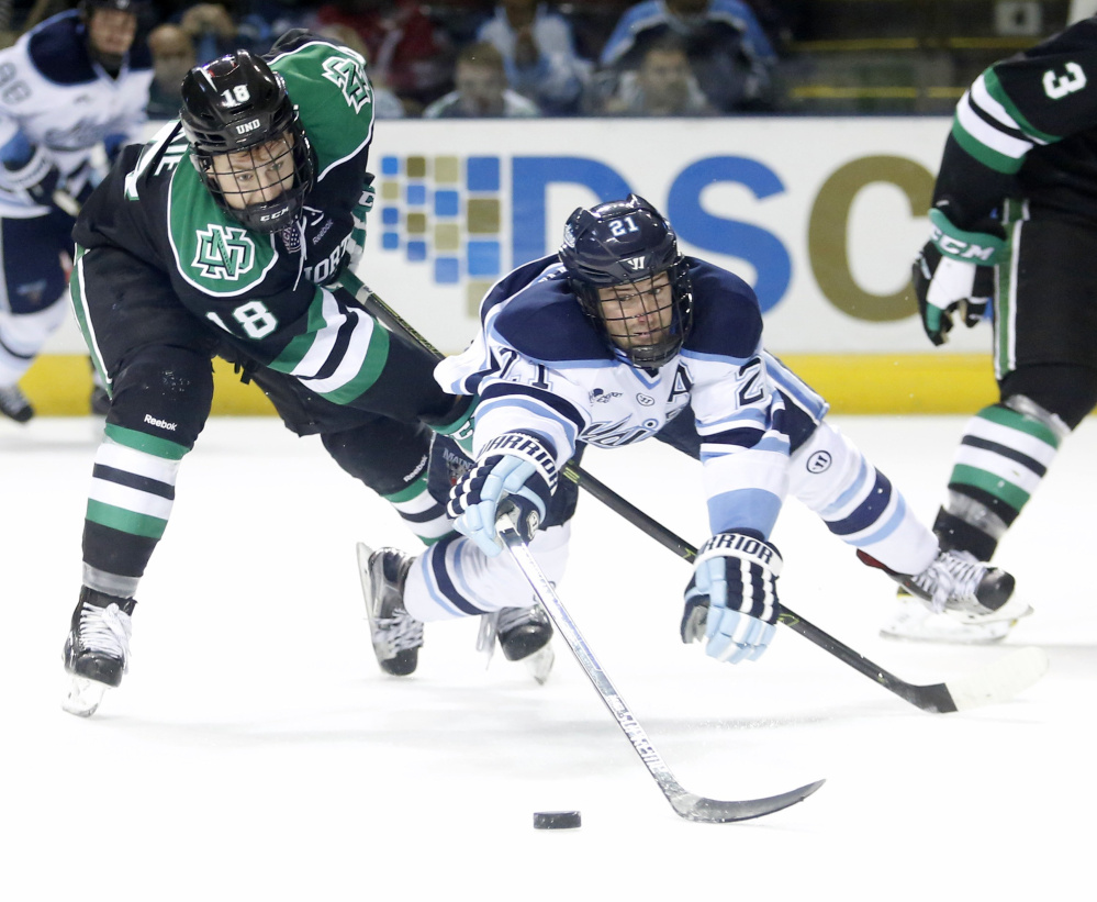 UMaine's Cam Brown reaches for the puck in a game against North Dakota last fall. The team ended its season last weekend with an 8-24-6 record, the second worst in Black Bear history.
