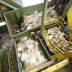 """A conveyor belt carries recyclable materials at ecomaine's Portland site. """"It costs money to run a truck around and pick up materials and process them,"""" says George MacDonald with the Maine DEP. """"And if the final value isn't there, a company has to figure out how to support the services."""""""