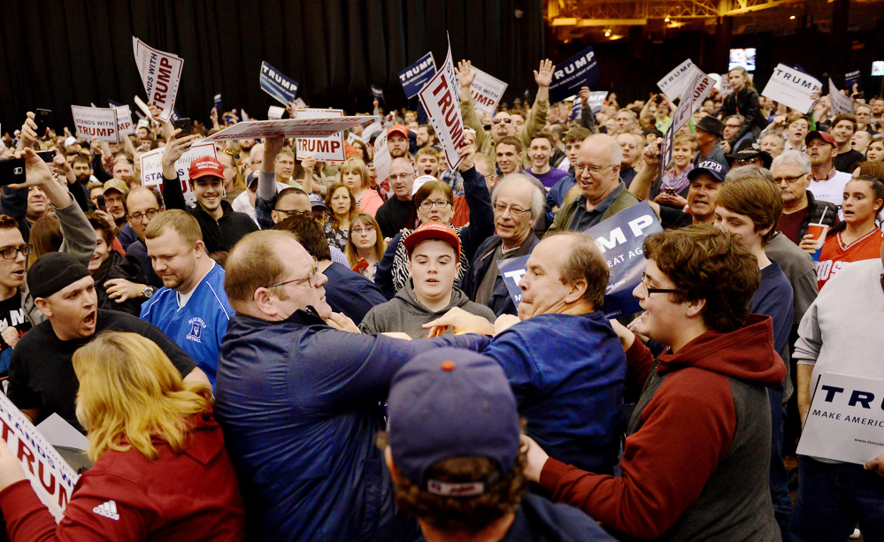 A protester, center left, and a Trump supporter, center right, scuffle during a rally for Republican presidential candidate Donald Trump Saturday held at the I-X Arena in Cleveland, Ohio.